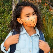 School Age girl wearing orange face mask