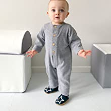 Baby taking first steps in Dotty Fish Soft Sole Baby Shoes, navy blue shoes with white star,