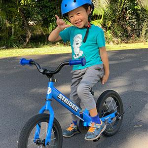 Young boy riding blue 14x strider bike