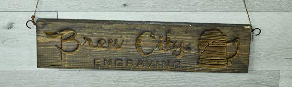 Brew City Engraving logo engraved on wood sign hanging from a chain