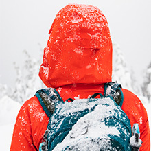 Person with snow covered backpack and orange jacket