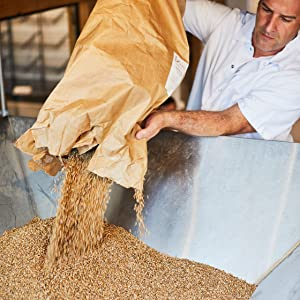 One Mighty Mill - Man pouring flour into mill