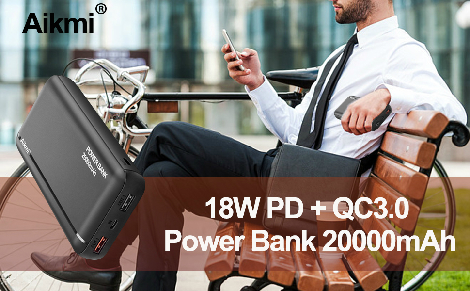 A man was sitting in a chair playing with his cell phone while charging with a 20000 mAh power bank