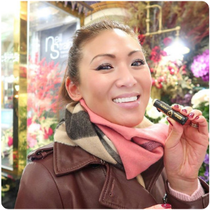 A woman applying her Aubio Hydrating Lip Balm as she smiles