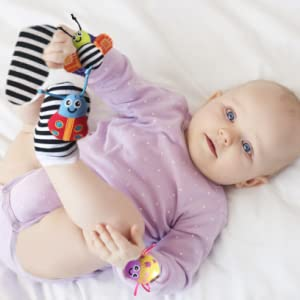 baby girl lying on back playing with foot which has baby cheeks rattle set bracelets and socks