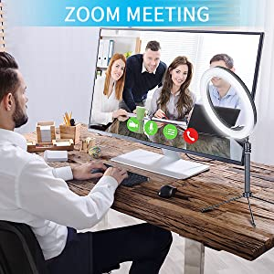 A man is in Zoom meeting, and a ring light with tripod on the desk.