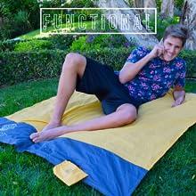 boy on phone laying on the orange ECCOSOPHY pocket blanket in a garden