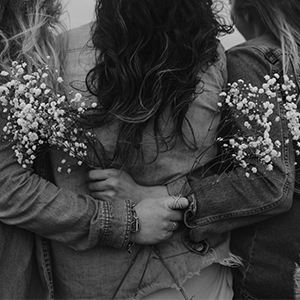 Group of friends holding flowers and wearing jewerly