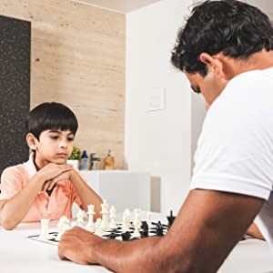 boy playing chess with father concentrated