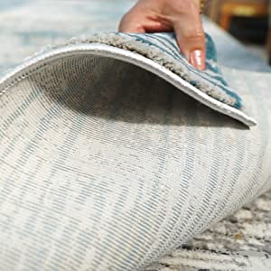 woman with laptop on top of soft area rug