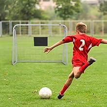 a kid shoot the ball towards the soccer goal
