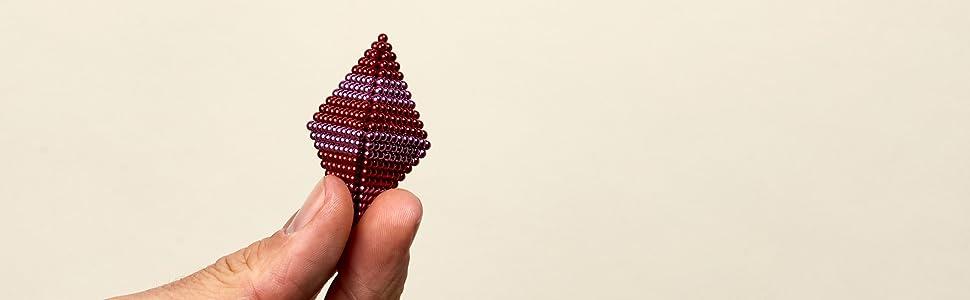 cherry pop speks in a diamond shape in a male hand