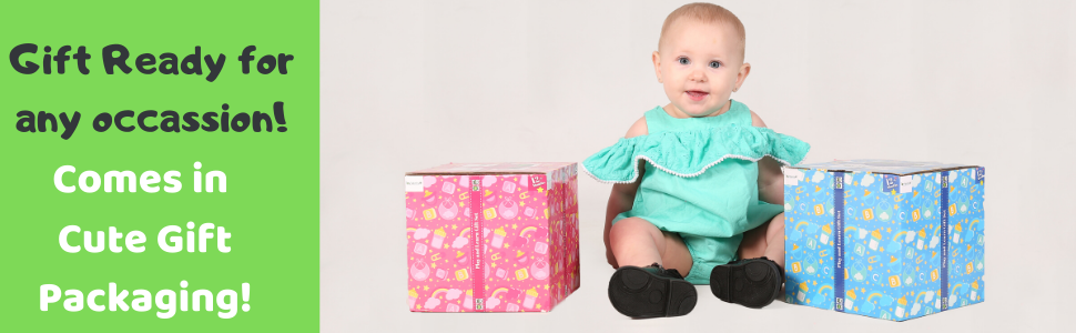Little baby girl smiling sitting between two gift boxes: pink on the left, blue on the right