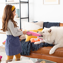 Young girl and large white dog playing with a zippypaws toy