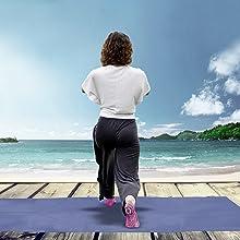 Woman doing kneeling yoga pose in pink Pakari socks on boardwalk in front of sea.