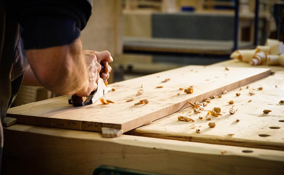 amish woodworker hand planes a piece of lumber