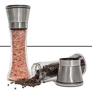 Salt shaker standing up, pepper shaker on the ground with some pepper spilling out