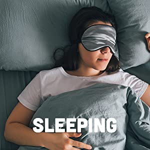 White woman in a white tee shirt sleeping on a bed with gray linens and a sleeping mask