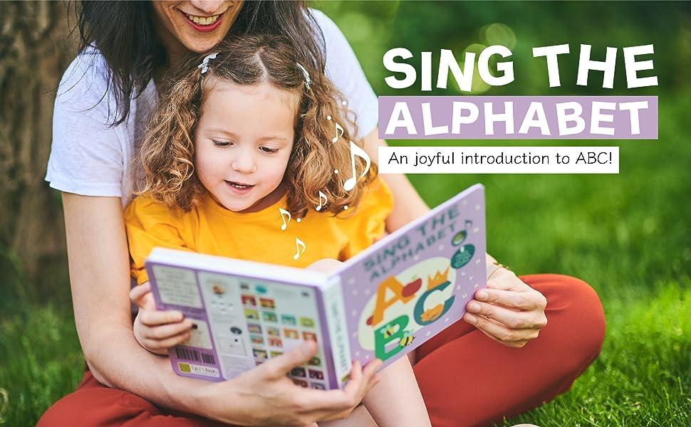 toddler girl reading abc sound book