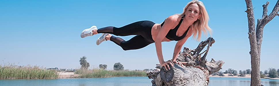 women planking exercising on a wooden stump
