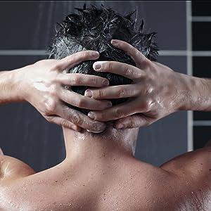 Mann in der Dusche beim Haarewaschen