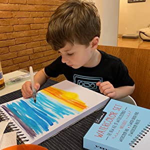kassa watercolor set being used by a kid to paint a beautiful sunset with water brushes