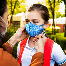 Mother is putting blue face mask to her daughter's face