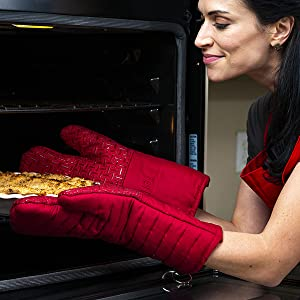 Model using oven mitts to remove a pie from the oven.