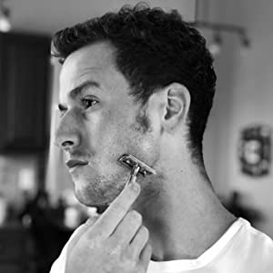 Attractive man shaving his face with American Shaving Co. Pre-Shave Oil.