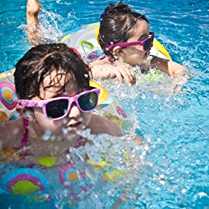 Two young girls playing in a pool with safety floaties