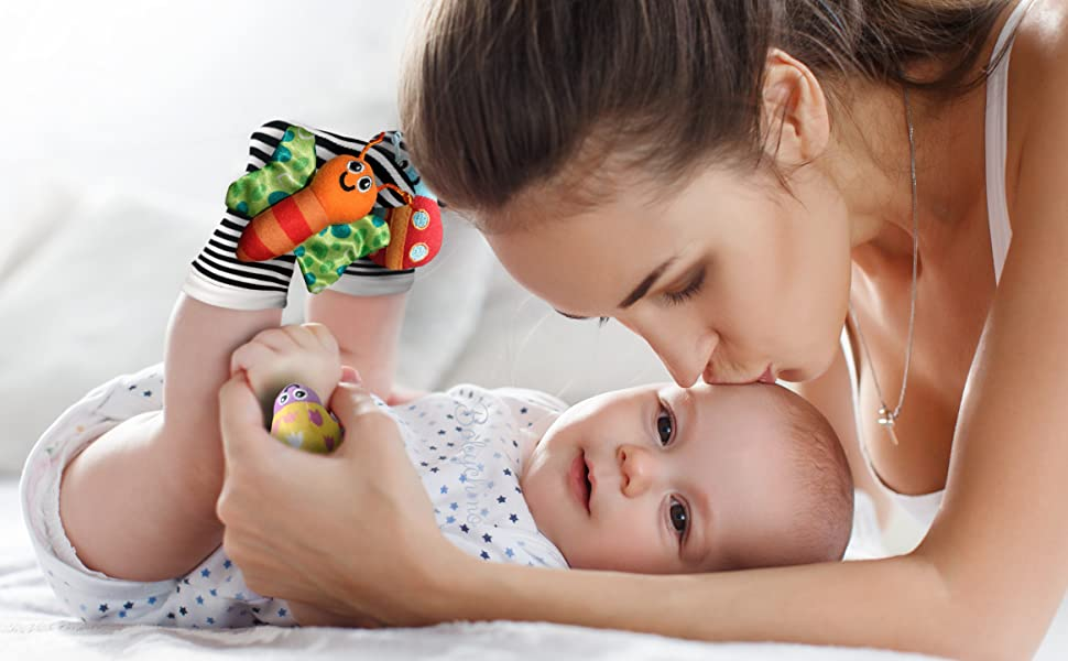 Mother kissing baby on forehead. Baby wearing cute garden bug rattle socks