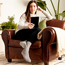 Woman sitting at home on couch with yoga non slip socks