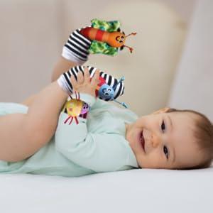 baby boy lying on back wearing baby cheeks rattle set. Happily playing with buy on rattle sock