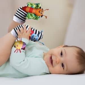 Baby boy smiling and holding his foot. He is wearing the baby foot finder rattle socks