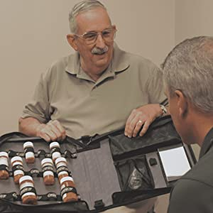 patient showing doctor medication binder with pill bottles and medical records