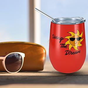 Fiesta Red Orange Sun Living the Dream Wine Tumbler on Table next to Sunglasses