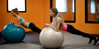 woman-in-purple-sports-bra-and-black-leggings-doing-yoga