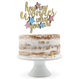gold how we wonder what you are cake topper with pink and blue stars shown on a naked cake