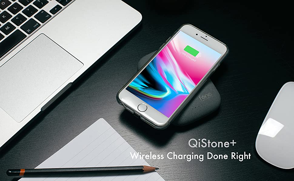 QiStone+ charging a phone, on a desk with a laptop.