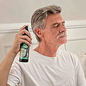 Image of a man spraying the oil on his temples before going to sleep