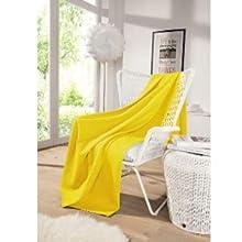 Die kuschelige und große Decke in gelb ist die perfekte, praktische Dekoration.
