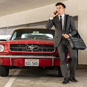 Broker leaning on red ford satisfied with his deal and feeling confident in his attire and bag