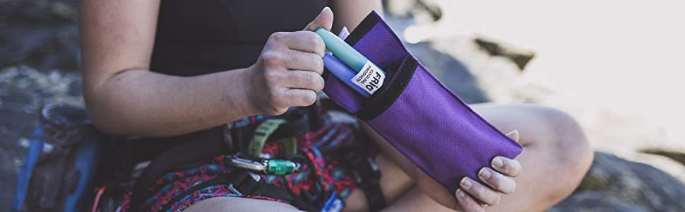 Rock climber holding FRIO wallet and pulling out an insulin pen
