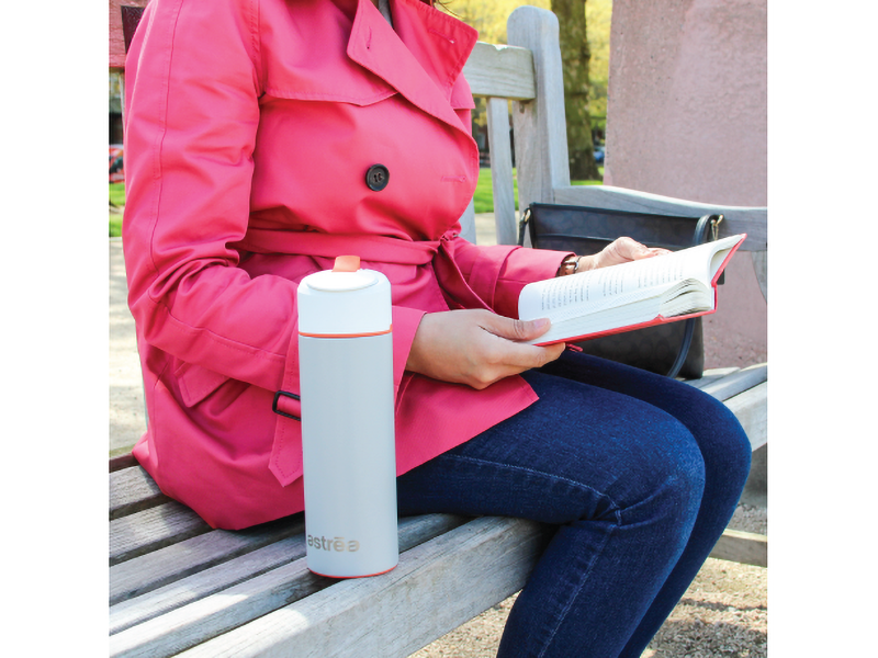 Someone reading on a park bench with the astrea ONE water bottle