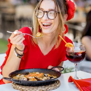 woman eating spanish paella from enameled paella pan machika authentic recipe kitchenware cookware