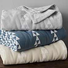 a stack of blankets. bottom is sand colored, second is blue, and top is grey