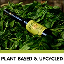 Bottle of Salute Santé Grapeseed Oil lying on a pile of fresh mixed greens piled into a basket.