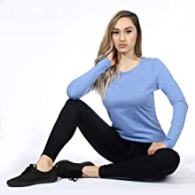 The image shows a model sitting down with elbow propped on knee wearing a Topstitch Under Scrub Tee.
