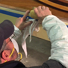 Sanding TotalBoat TotalFair Epoxy Fairing Compound on the side of a wooden kayak.