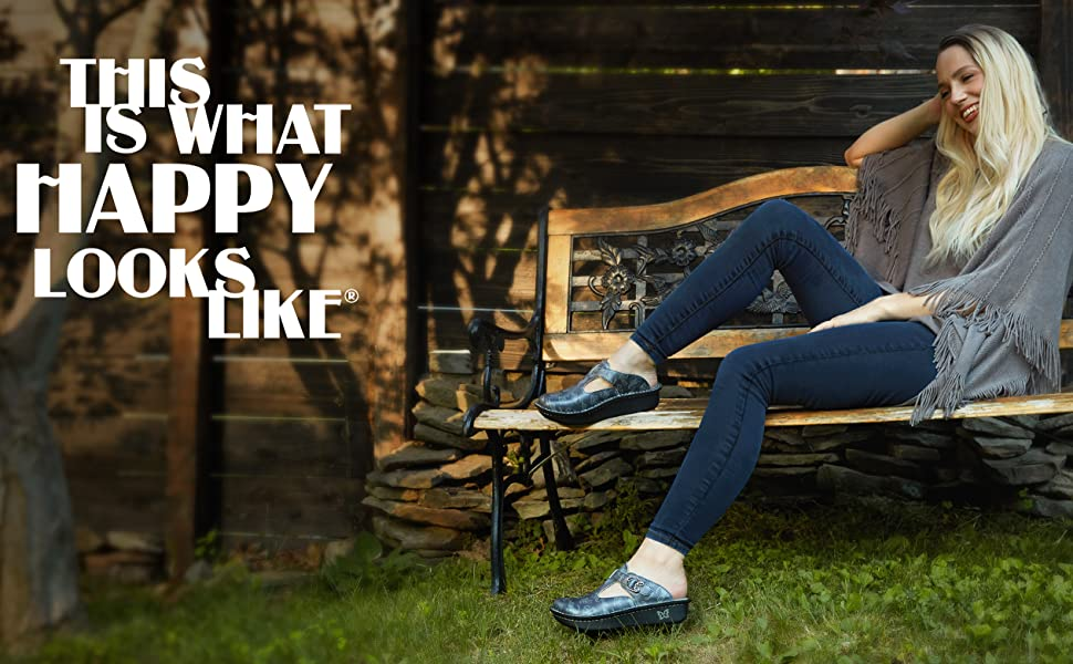 """""""This is what happy looks like"""" - A woman smiling sitting on a bench with her Alegria shoes"""